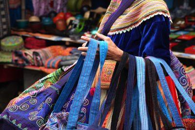 Zelo pisana oblačila so značilna za Cvetlične Hmonge - gospa prodaja ročno izdelane torbice