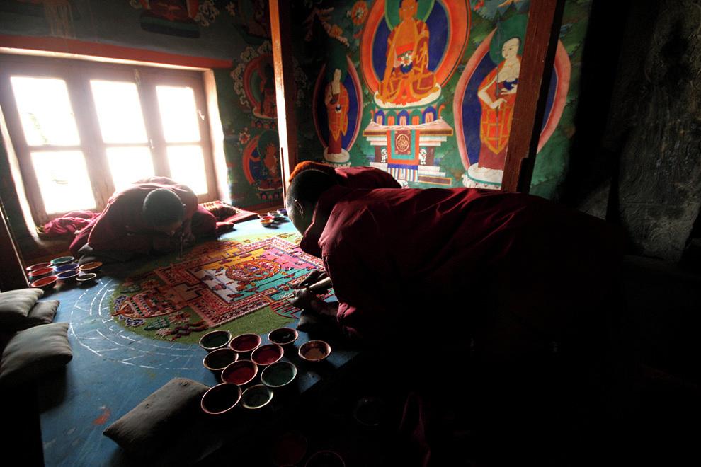 Tibetanski menihi, zatopljeni v izdelavo peščene mandale.